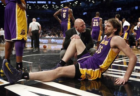Los Angeles Lakers' Pau Gasol sits on the floor with a member of the Lakers medical staff after suffering an injury to his right leg in the