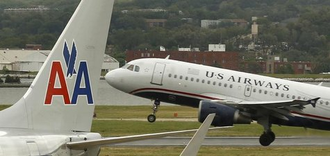 A US airways plane takes off behind an American Airlines jet at Ronald Reagan National Airport in Washington April 23, 2012. REUTERS/Kevin L
