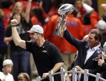 Baltimore Ravens head coach John Harbaugh (L) celebrates as team owner Steve Bisciotti holds up the Vince Lombardi Trophy after defeating th