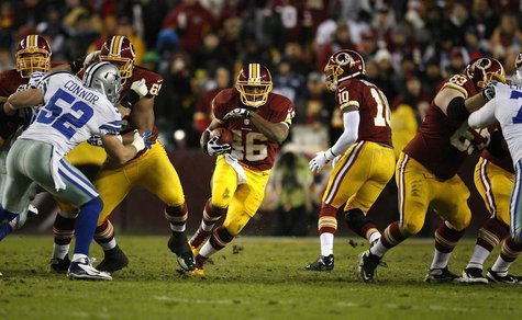 Washington Redskins running back Alfred Morris (C) runs through the Dallas Cowboys line during the first half of their NFL football game in