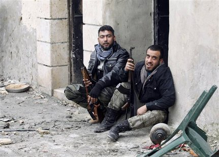 Free Syrian Army fighters carry their weapons as they sit on the ground at the Sheikh Saeed district, near a cement factory in Aleppo, Febru