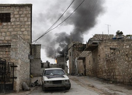 Smoke rises behind a car decorated with an Islamist flag in the Sheikh Saeed district, near a cement factory in Aleppo, February 7, 2013. RE