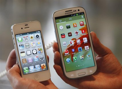 An employee holds Apple's iPhone 4s (L) and Samsung's Galaxy S III at a store in Seoul in this file photo from August 24, 2012. REUTERS/Lee