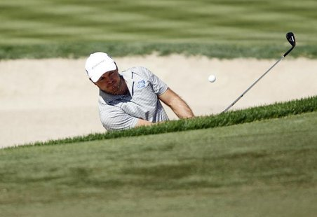 Richard Sterne of South Africa hits out of a bunker at the third green during the fourth and final round of the Dubai Desert Classic at the