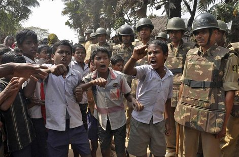 Children shout slogans as police stand guard during a protest against land acquisition at Gobindpur village in Jagatsinghpur district, in th