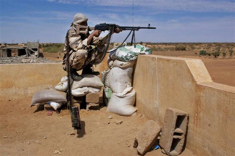 A Tuareg soldier in the Malian army aims his rifle at a checkpoint along a road leading to the border with Niger in the northern city of Gao