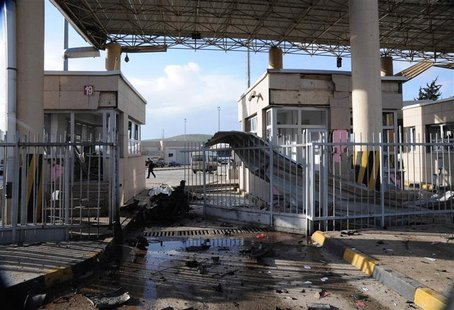 A man walks past a damaged gate after an explosion at Cilvegozu border gate on the Turkish-Syrian border in Hatay province February 11, 2013