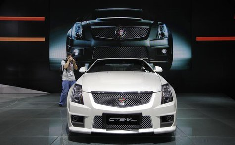A photographer takes pictures of a Cadillac CTS-V Coupe during the media preview of 10th China International Automobile Exhibition in Guangz