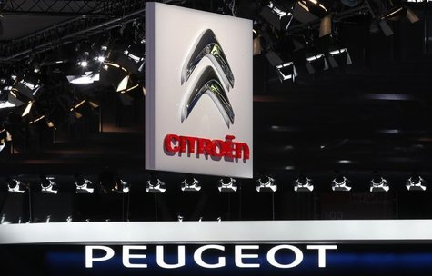 Peugeot and Citroen logos are seen over the French carmakers' showcases on media day at the Paris Mondial de l'Automobile, September 28, 201