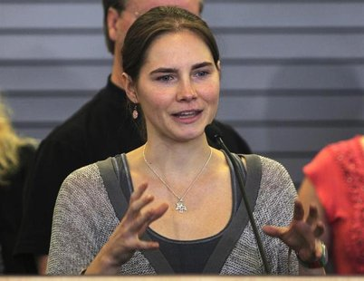 Amanda Knox gestures while speaking during a news conference at Sea-Tac International Airport, Washington after landing there on a flight fr