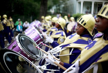 Members of the St. Augustine High School band march down St. Charles Avenue as the Krewe of Mid-City parades during the weekend before Mardi
