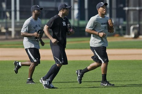 New York Yankees outfielders (from L) Melky Mesa, Curtis Granderson and Thomas Neal take to the field during an informal workout at the team