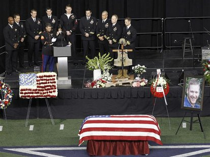 Taya Kyle is steadied by a Marine while addressing friends and family during a memorial service for slain husband and former Navy SEAL snipe