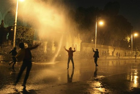 Protesters opposing Egyptian President Mohamed Mursi and the Muslim Brotherhood chant anti-government slogans while police spray water on th