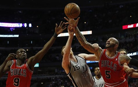 Chicago Bulls' Carlos Boozer (R) and teammate Luol Deng (L) battle San Antonio Spurs' Matt Bonner for a rebound during the first half of the