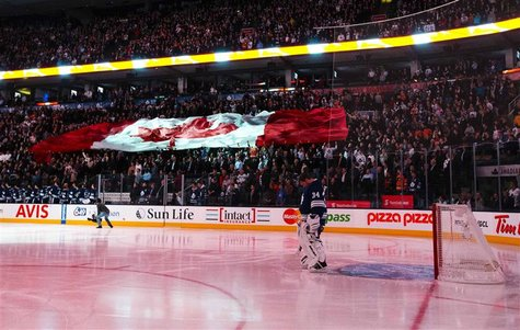 Toronto Maple Leafs goalie James Reimer stands while the Canadian national anthem is played as fans hold a giant Canadian flag before his te