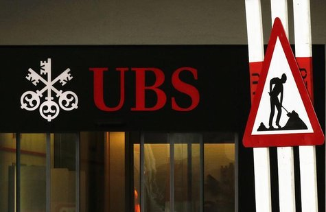 A woman woman walks past a construction road sign in front of a branch of Swiss Bank UBS in Lugano, southern Switzerland December 20, 2012.