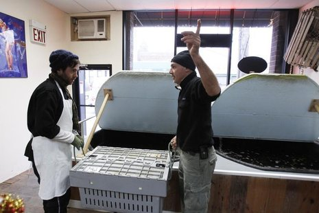 "Small-business owner Ralph Gorham (R) speaks to employee Elijah Ocean at his shop ""Redhook Lobster Pound"" in New York December 16, 2010. REU"