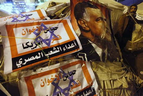 A protester opposing Egyptian President Mohamed Mursi walks outside tents near a picture of Egypt's former president Gamal Abdel Nasser duri