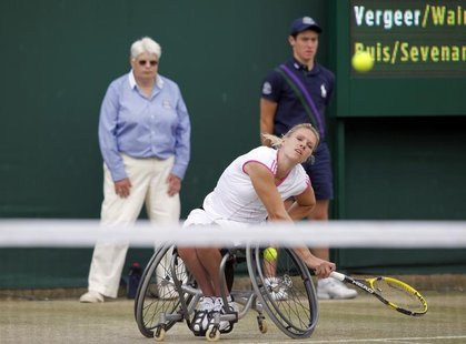 Esther Vergeer of the Netherlands serves, with her partner Sharon Walraven of the Netherlands (UNSEEN), to Marjolein Buis of the Netherlands