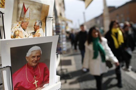 Tourists walk past pictures of Pope Benedict XVI displayed in a shop in Rome February 12, 2013.Pope Benedict stunned the Roman Catholic Chur