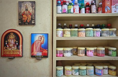 Pictures of Hindu gods hang beside a medicine rack inside a clinic in Pune in this August 27, 2012 file photo. REUTERS/Danish Siddiqui/Files