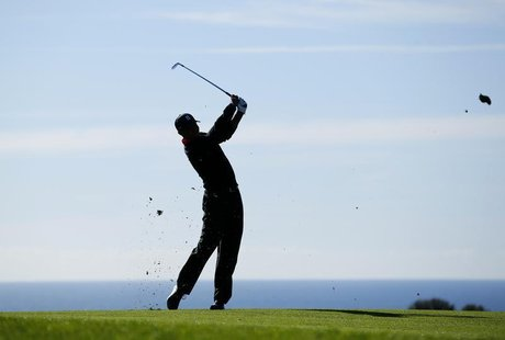 Golfer Tiger Woods hits his second shot off the 17th fairway during final round play at the Farmers Insurance Open in San Diego, California