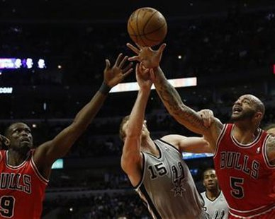 Chicago Bulls' Carlos Boozer (R) and teammate Luol Deng (L) battle San Antonio Spurs' Matt Bonner for a rebound during the first half of their NBA basketball game in Chicago, February 11, 2013. REUTERS/Jim Young