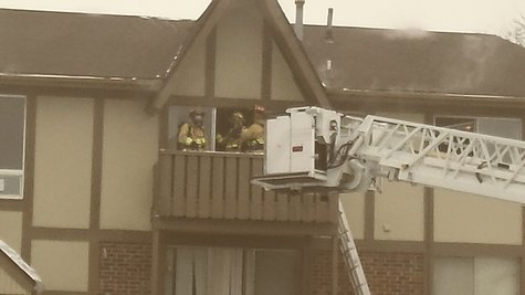 Firefighters on third story balcony