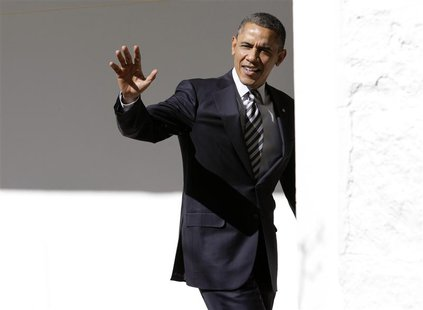 U.S. President Barack Obama waves to reporters as he walks through the colonnade of the White House in Washington February 12, 2013. REUTERS