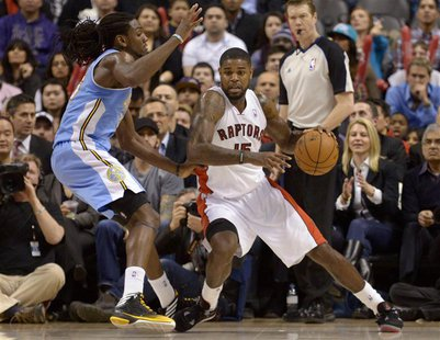 Toronto Raptors Amir Johnson (R) moves around Denver Nuggets Kenneth Faried during the second half of their NBA basketball game in Toronto F