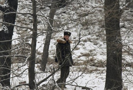 A North Korean soldier walks along the banks of Yalu River, near the North Korean town of Sinuiju, opposite the Chinese border city of Dando