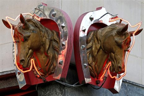 Metal horse heads outlined with neon lights are seen above a horsemeat butcher shop in Paris in this February 11, 2013 file picture. REUTERS