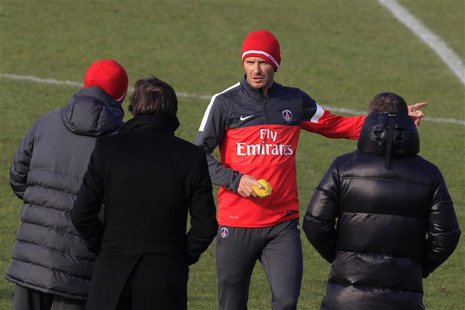 Paris Saint Germain's soccer player David Beckham (2ndR) speaks with Paris St-Germain sports director Leonardo (2ndL) and coach Carlo Ancelo