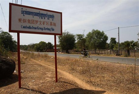 A man rides a motorcycle past a signboard for the Cambodia Iron Group at the Rovieng District in Preah Vihear province February 10, 2013. RE