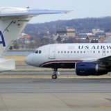A US Airways plane (R) taxis for takeoff past an American Airlines plane at the Ronald Reagan Washington National Airport in Arlington Count