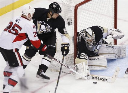 Pittsburgh Penguins goalie Marc-Andre Fleury (29) blocks a shot by Otttawa Senators' Chris Neil (25) as Penguins' Deryk Engelland (5) tries