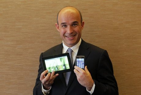 Research In Motion (RIM) Co-Chief Executive Jim Balsillie smiles as he poses with a PlayBook tablet computer (L) and a Blackberry Torch duri