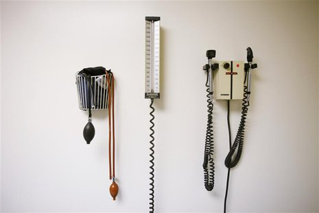 Devices used to take blood pressure, temperature, and examine eyes and ears rest on a wall inside of a doctor's office in New York March 22,