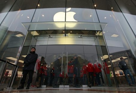 Security guards and staff stand at the entrance of an Apple store during the release of iPhone 5 in Beijing's Wangfujing shopping district,