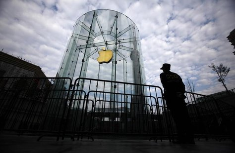 A security guard stands next to an Apple retail store during the release of the iPhone 5 in Shanghai December 14, 2012. REUTERS/Carlos Barri