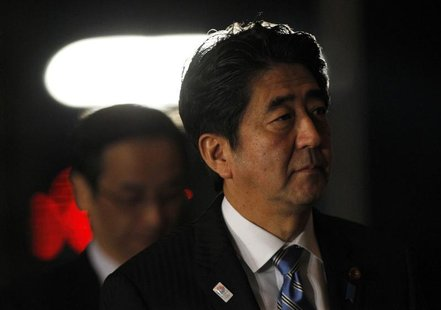 Japan's Prime Minister Shinzo Abe (R) arrives at his official residence for attending an advisory panel on restructuring legal infrastructur