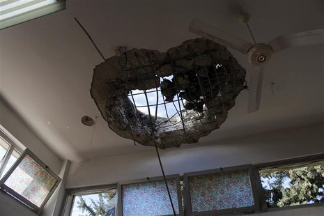 An opening in the ceiling of a room caused by shelling is seen at a building where patients of lbn Khaldoun psychiatric hospital were transf