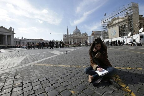 A media correspondent sits on the ground in Rome, as Saint Peter's Basilica at the Vatican is seen in the background, February 13, 2013. REU