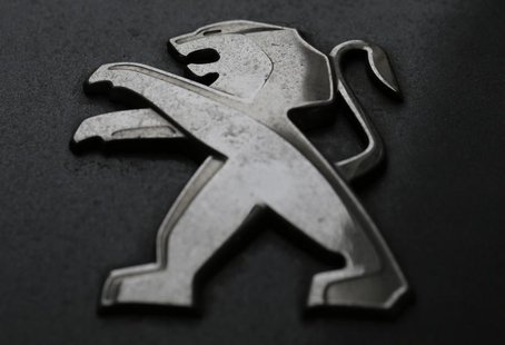 A company logo is seen on a Peugeot car parked in Paris, February 12, 2013. French carmaker PSA Peugeot Citroen is due to post its 2012 resu