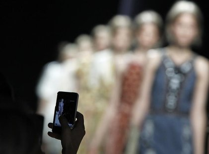 A woman uses her mobile phone to shoot a video during the Bottega Veneta Spring/Summer 2013 collection at Milan Fashion Week September 22, 2