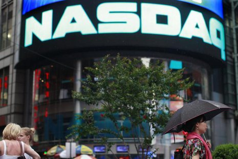 People walk outside the Nasdaq Market site in New York's Times Square, July 23, 2012. REUTERS/Brendan McDermid
