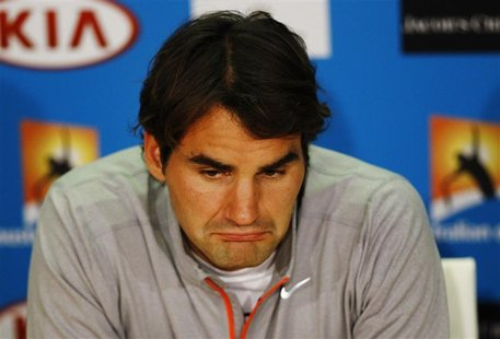 Roger Federer of Switzerland attends a news conference after he was defeated in his men's singles semi-final match by Andy Murray of Britain