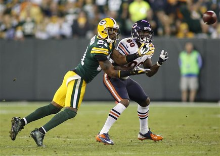 Green Bay Packers cornerback Charles Woodson (L) intercepts the ball against Chicago Bears wide receiver Earl Bennett (80) in the second hal