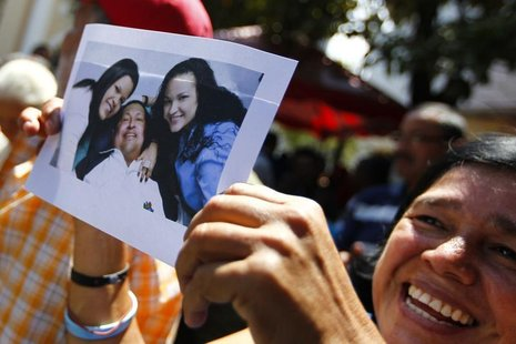 A supporter of Venezuelan President Hugo Chavez holds a copy of a photograph of Chavez released by the Ministry of Information, during a gat